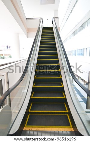 Escalator with yellow strips and glassy stair railing leading - stock photo