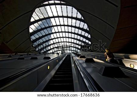escalators on London Underground (The Tube); skyscraper office block visible through glass roof - stock photo
