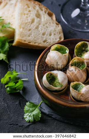 Escargots de Bourgogne - Snails with herbs butter, gourmet dish, in traditional ceramic pan with parsley and bread on stone slate board over black textured background. Close up