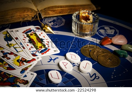 esoteric table with astrological wheel, magic pendulum, tarots, runes, healing stones and Iching coins - stock photo