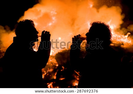 ESPELO, THE NETHERLANDS - APR 05, 2015: Two man drinking beer in front of a huge bonfire, a tradition with easter in North-West Europe.