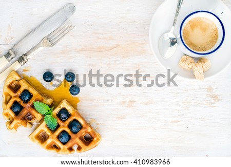 Espresso coffee cup and soft belgian waffles with fresh blueberries and marple syrup on white painted wooden board over light blue background. Top view, copy space, horizontal - stock photo