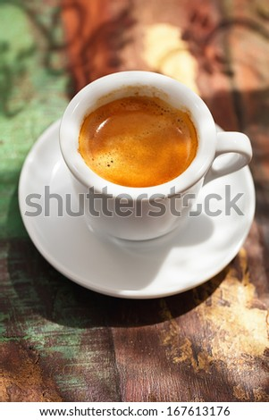 espresso coffee cup on rustic table with sun light and shadows - stock photo