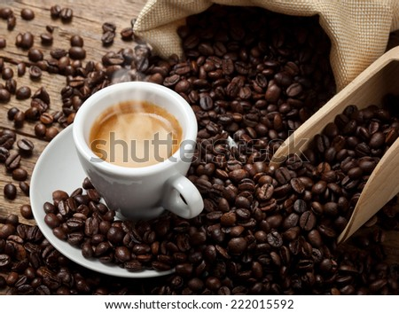 Espresso coffee cup with coffee beans on wooden table. - stock photo
