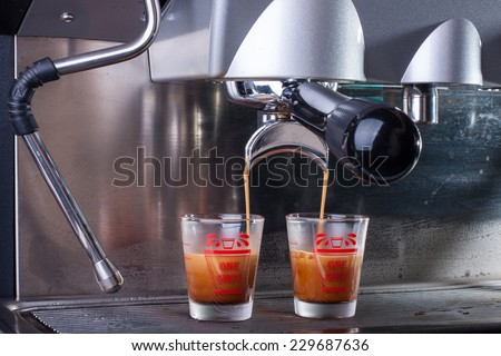 Espresso coffee machine, Coffee is pouring in a glass of coffee machine. - stock photo