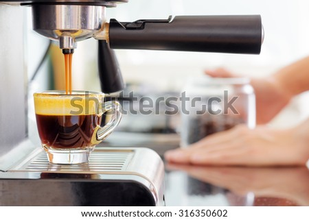 Espresso coffee machine in kitchen. Jets of hot invigorating coffee pouring into cup. - stock photo