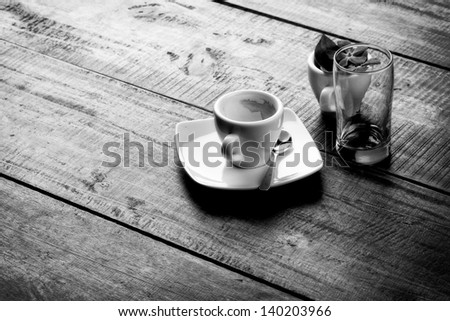 Espresso empty cup on wooden table top, monochrome image. - stock photo