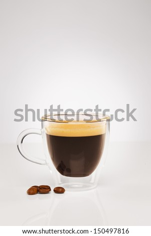 espresso in a glass cup with coffee beans on gray background