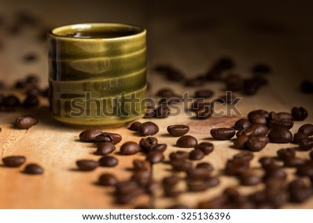 Espresso in coffee cup with coffee beans on desk wood