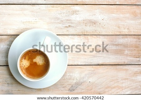 Espresso in the cup on the wooden background, overhead horizontal view. Brown Italian coffee espresso.