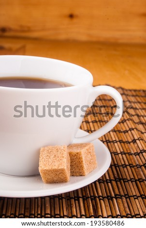 espresso in white cup with brown sugar on table covered with wooden mat