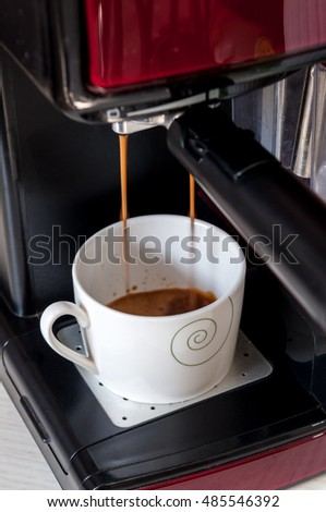 Espresso machine serving coffee in a cup.
