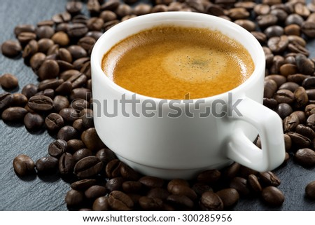 espresso on coffee beans background, close-up, selective focus, horizontal - stock photo