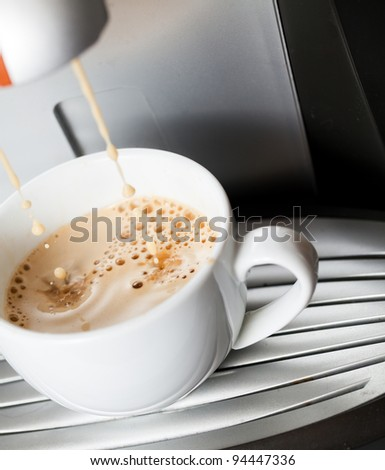 Espresso pouring into a white cup - stock photo
