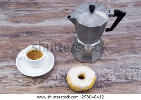 Espresso with a glazed donut on a wooden table from above with copy space - stock photo