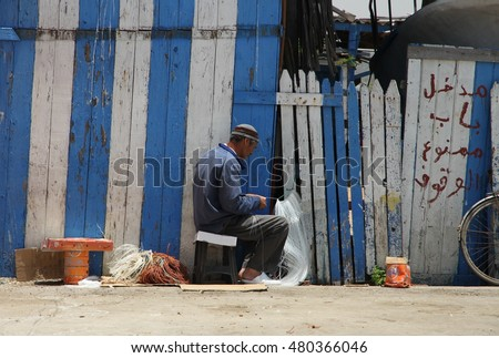 ESSAOUIRA, MOROCCO - JULY 4: A local fisherman repairing fishing nets at the historical port of Essouira, Morocco on the 4th July, 2015.