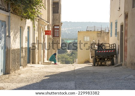 ESSAOUIRA, MOROCCO, MARCH 14, 2014. A Muslim woman in a green gown sitting and looking into the distance in the stairs of a building in the outskirts of Essouira Morocco, on March 14th, 2014. - stock photo