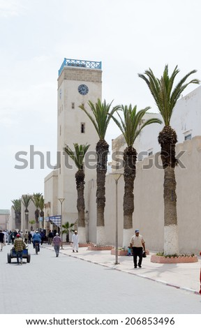 ESSAOUIRA, MOROCCO - MAY 14, 2014: Local berbers walking outside of citadel walls showing clock tower and palm trees. Essaouira, Morocco. May 14, 2014.