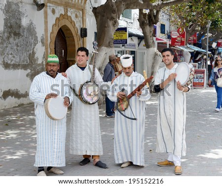 ESSAOUIRA, MOROCCO - MAY 12, 2014: Musicians playing traditional instruments in the street for tourists and shoppers. Essaouira, Morocco. May 12, 2014. - stock photo
