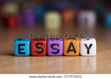 essay words with dices on wooden table - stock photo