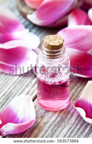 Essence Bottle, Aromatherapy Essential Oil Bottle and Soft Pink Petals - stock photo