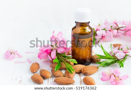 Essential almond oil, flowers and nuts on a white background.