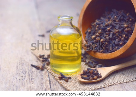 Essential aroma clove oil in a glass bottle with dried cloves on wooden spoon and  background. - stock photo