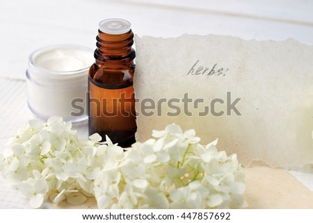 Essential aroma oil bottle, white natural cosmetic skin care cream, fresh flowers, paper note. Beige tones, soft focus.  - stock photo