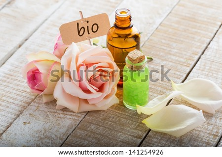Essential aroma oil from roses  on wooden background. Organic/bio product. Selective focus. - stock photo