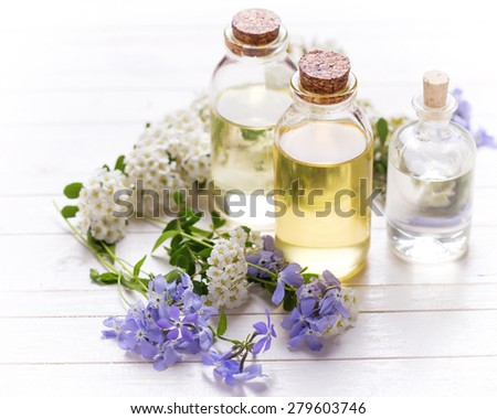 Essential aroma oil on  white painted wooden background. Selective focus. Place for text. Toned image. - stock photo