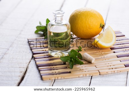 Essential aroma oil with lemon and mint  on wooden background. Selective focus. - stock photo