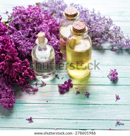 Essential aroma oil with lilac on  turquoise painted wooden background. Selective focus. Place for text. Square image. - stock photo