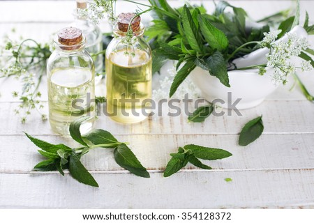 Essential aroma oil with mint  on white painted wooden background. Selective focus. Place for text.