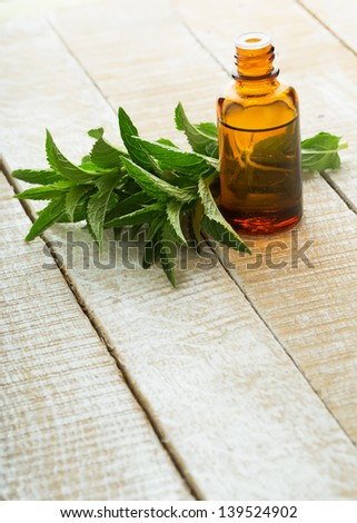 Essential aroma oil with peppermint on wooden background. Selective focus.
