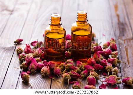 Essential aroma oil with roses on wooden background. Selective focus is on right bottle. - stock photo