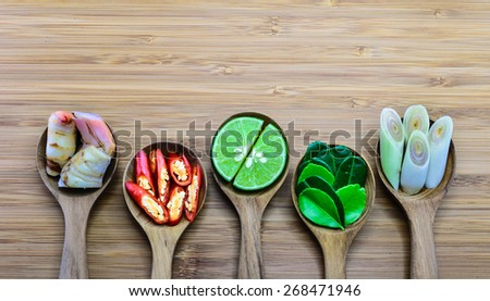 Essential ingredients of Tom Yum, Thailand famous food in wood spoon on wood background. From left: Galangal, Chili lime,  kaffir lime leaves, lemongrass - stock photo