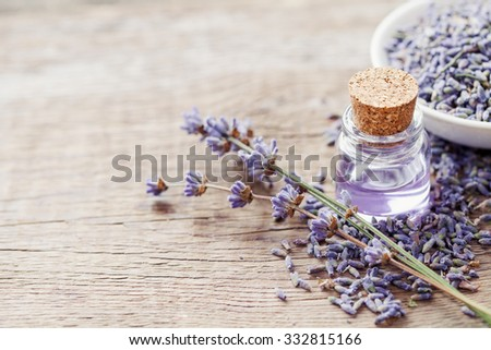 Essential lavender oil and dry lavender flowers. Selective focus. - stock photo