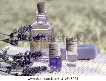 Essential lavender oils and  herbal soap with fresh flowers - stock photo