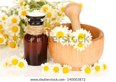 Essential oil and chamomile flowers in mortar close up - stock photo