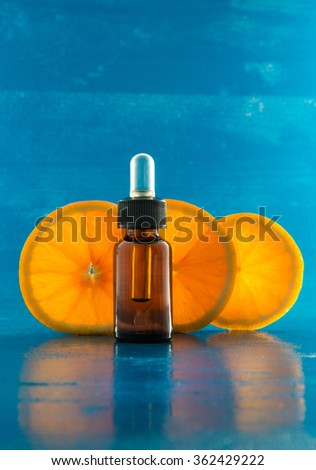 Essential oil bottle on blue background with backlighting - stock photo