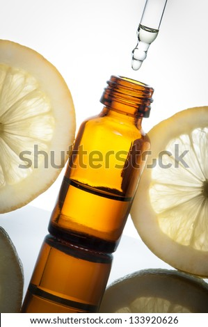 Essential oil bottle with lemons - stock photo