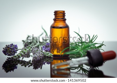 Essential oil bottle with rosemary and lavender flowers