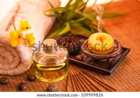 Essential oil bottles, towels, candle and flower in health spa for spa treatment. [Focus at the oil bottle] - stock photo