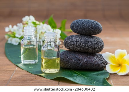 Essential Oil, flower, pebble stone on green leaf, blur background for spa - stock photo