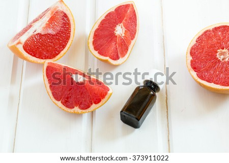Essential oil in glass bottle with fresh, juicy grapefruit. Spa concept.  Selective focus. - stock photo
