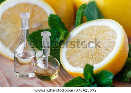 Essential oil in glass bottle with fresh, juicy lemon fruit and green leaves of mint-beauty treatment. Spa concept. Selective focus. - stock photo