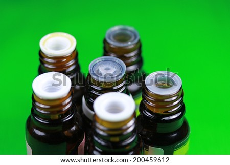 essential oil jars close up on a green background - stock photo