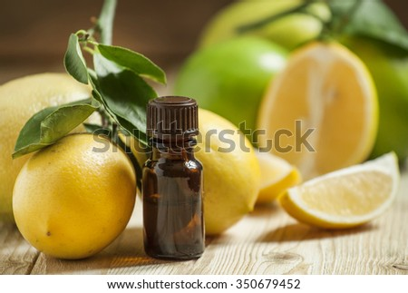 Essential oil of lemon and fresh lemons on the old wooden background, selective focus - stock photo