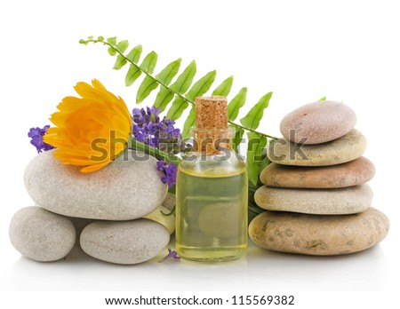 Essential oil with lavender, calendula flowers and pile of stones on a white background