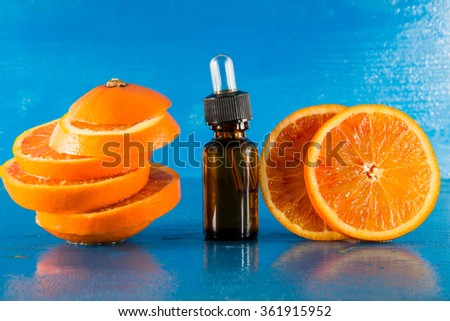 Essential oil with orange slices, bottle and dropper, with blue background (horizontal)